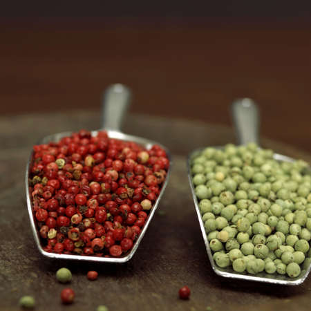 juxtaposing: Red and green peppercorns in scoop, close-up