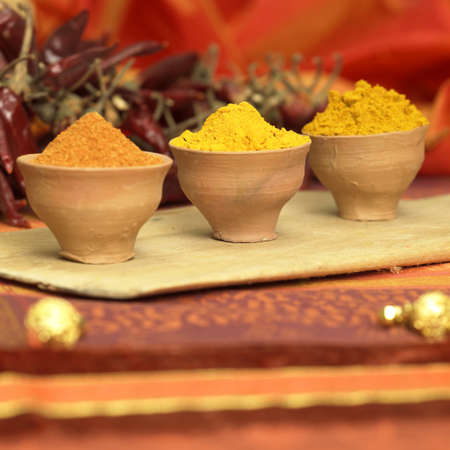 exotism: Curry, curcuma and chilli powder in bowls, close-up