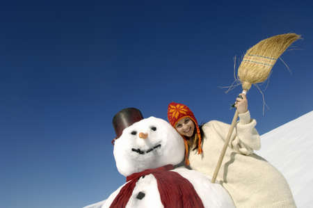 kind hearted: Young woman leaning on snowman, portrait