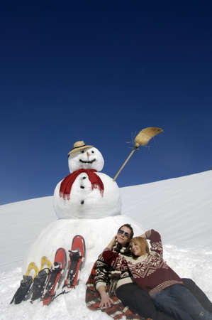 diverted: Couple sitting by snow man with snow shoes