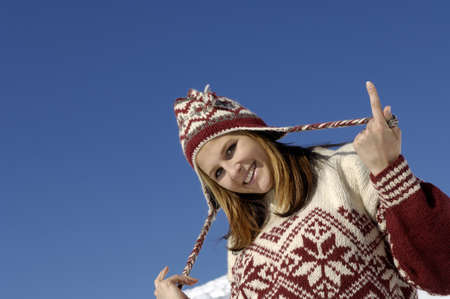 kind hearted: Young woman pulling woolly hat, smiling, portrait, close-up LANG_EVOIMAGES