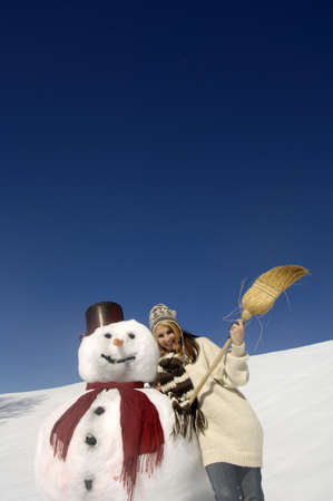diverted: Young woman leaning on snowman, holding broom, low angle view