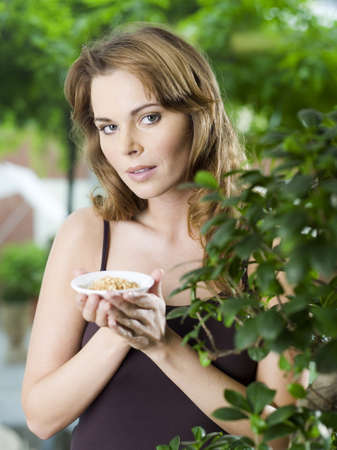 confiding: Woman with spice in bowl by plant
