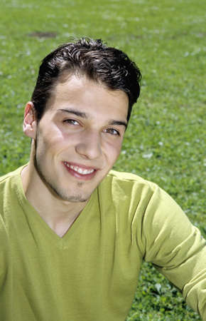 aplomb: Young man sitting on grass, portrait, close-up