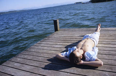 easygoing: Young man relaxing on jetty, elevated view