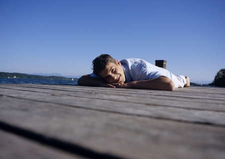 unworried: Young man lying on jetty, smiling