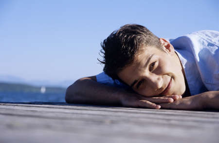 kind hearted: Young man lying on jetty, smiling, close-up LANG_EVOIMAGES