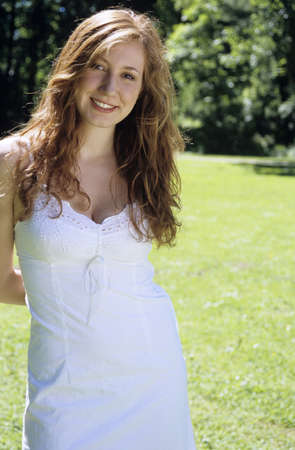 unworried: Young woman in white dress standing in garden, smiling, portrait