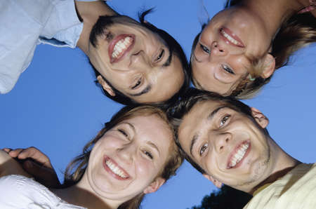 embracement: Four young people in huddle, upward view, portrait