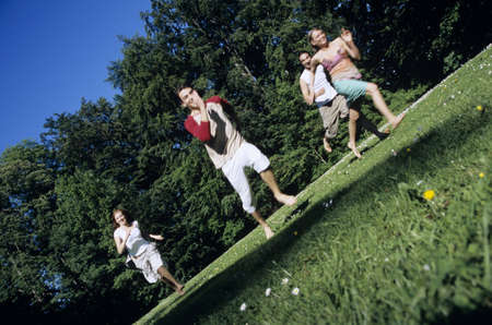 low spirited: Four young people running through garden LANG_EVOIMAGES