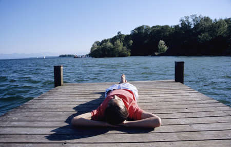 unworried: Young man relaxing on jetty, elevated view