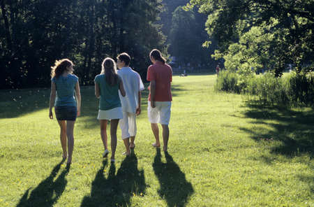 kind hearted: Four young people walking in park, rear view LANG_EVOIMAGES