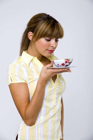 gratified: Young woman holding tea bowl