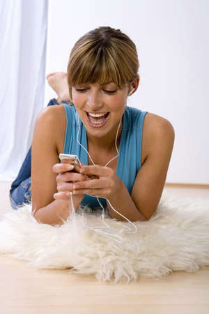 25 30 years women: Young woman listening to MP3 player,smiling