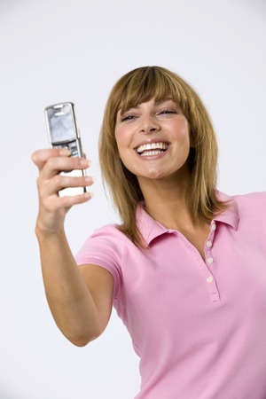 conceited: Young woman photographing self using camera phone,smiling,close-up LANG_EVOIMAGES