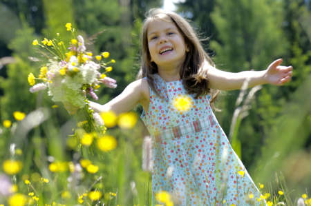 kind hearted: Girl with bunch of flowers in summer meadow