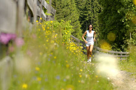 mirthful: Young woman jogging in meadow,smiling