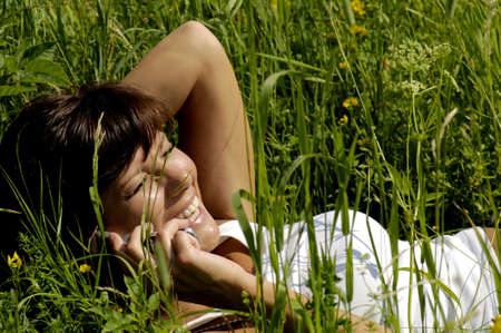 kind hearted: Woman lying in field using mobile phone,smiling,elevated view