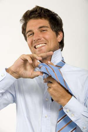 mirthful: Young man binding tie,portrait
