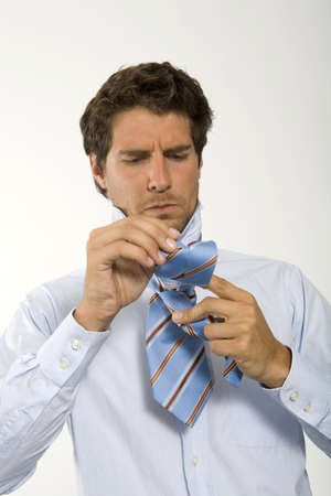 knotting: Young businessman getting ready,knotting tie,close-up