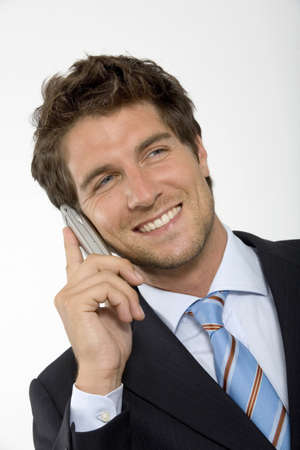 gratified: Young businessman using mobile phone,smiling,close-up