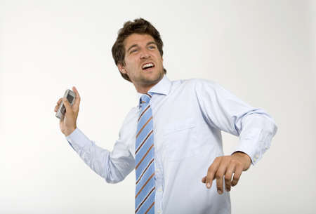 infuriate: Young businessman throwing mobile phone,close-up LANG_EVOIMAGES