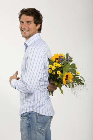 caching: Young man holding bouquet of flowers behind back,smiling,close-up,portrait