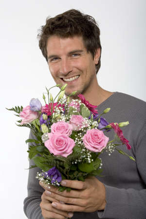hope indoors luck: Young man holding bouquet of flowers,smiling,close-up,portrait