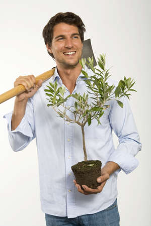 hope indoors luck: Young man carrying pot plant and spade,close-up