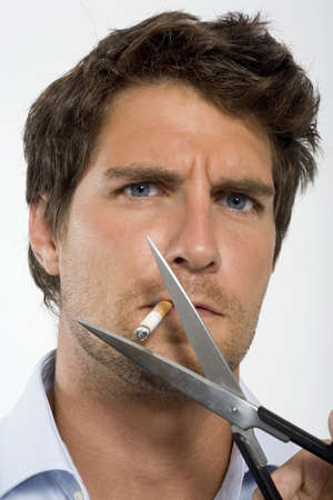 cut off head: Young man cutting cigarette with scissors,close-up,portrait LANG_EVOIMAGES