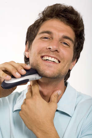 mirthful: Young man shaving with electric razor,close-up,portrait