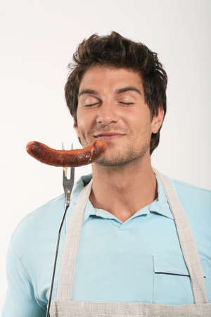 bratwurst: Young man smelling grilled sausage on fork,eyes closed,close-up