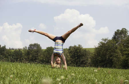 non moving activity: Teenage girl (13-15) making handstand in meadow