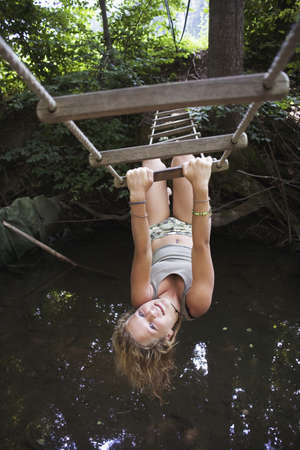 14 15 years: Teenage girl (13-15) hanging upside down on rope-ladder