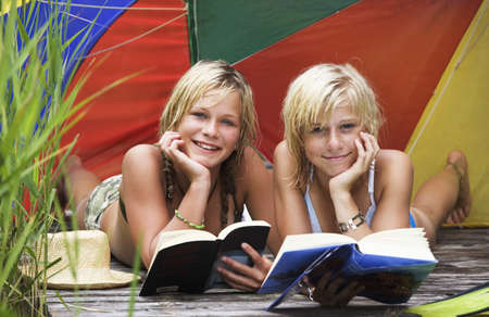 14 15 years: Teenage girls (13-15) lying under sunshade on jetty, reading book, portrait