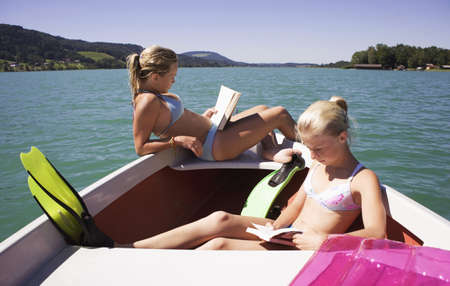 flippers: Girls (13-15) sitting on boat, reading, side view