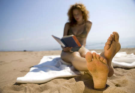 curved leg: Young woman on beach,reading book