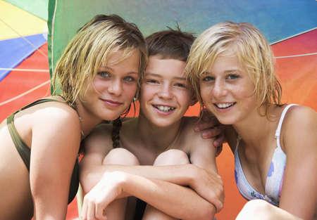 pubertad: Las adolescentes (13 a 15) y un ni�o sentado bajo la sombrilla, primer plano, retrato