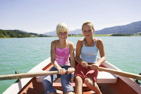 mirthful: Teenage girls (13-15) rowing boat, smiling, portrait