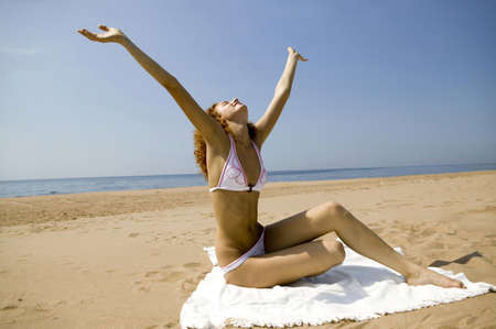 gentle dream vacation: Young woman sitting on bath towel,stretching arms