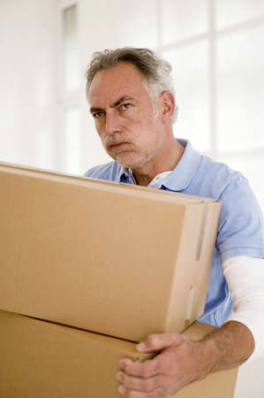 grizzled: Mature man holding carton,looking away,close-up