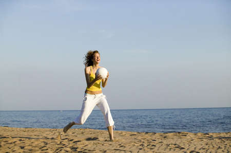 mirthful: Young woman running on beach,holding ball,laughing LANG_EVOIMAGES