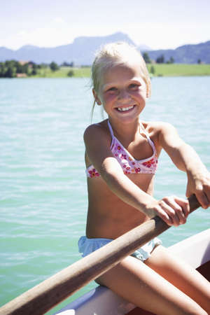 7 8 years: Girl (8-9) rowing boat, smiling, close-up, portrait