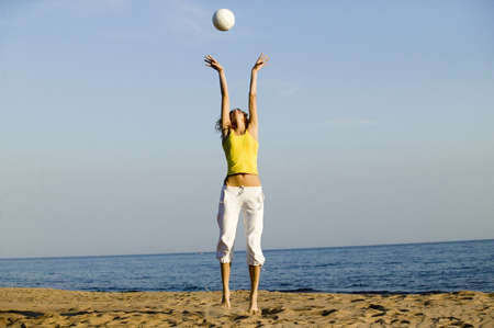 easygoing: Young woman playing with ball on beach,jumping