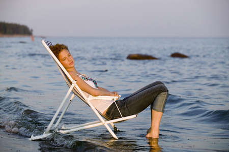 asleep chair: Young woman resting in deck chair on beach,side view