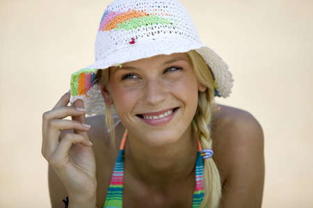 sun hat: Young woman on beach wearing sun hat,close-up