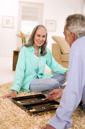 parlour games: Mature couple playing backgammon in living room,smiling