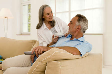 confiding: Mature couple in living room,smiling,close-up
