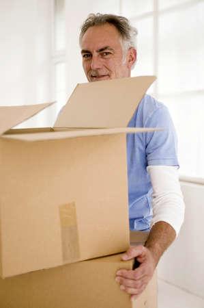 exert: Mature man holding carton,portrait,smiling LANG_EVOIMAGES