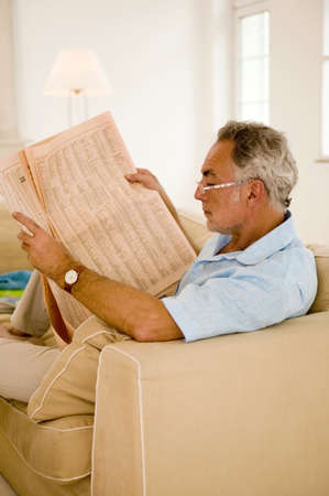 early fifties: Mature man reading newspaper on sofa,side view,close-up LANG_EVOIMAGES